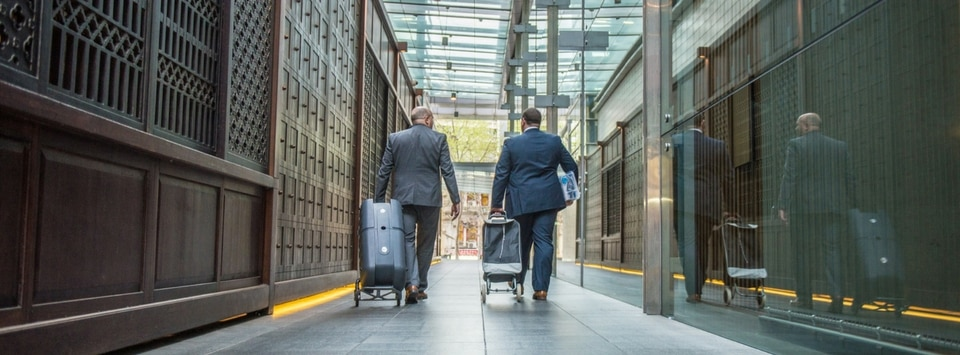Two business travelers walking down a hallway
